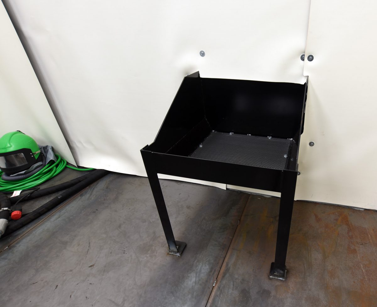 A floor-mounted media reclaim hopper. Hoppers can be recessed (deep pit required) or floor mounted (no pit required). The reclaim system then feeds the recycled media back into the blast machine.